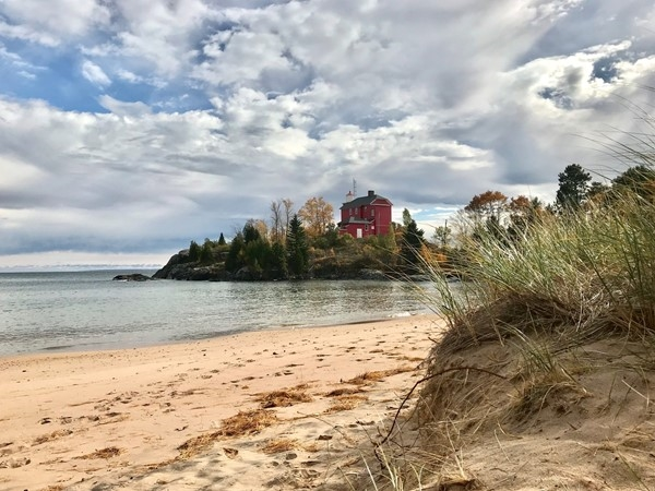 Marquette Harbor Lighthouse shines on a cool October day. Beautiful beach and landscape