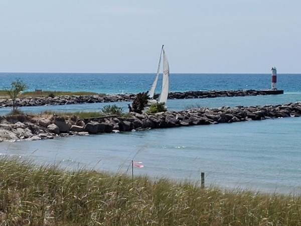 Sailboat going out from Arcadia Lake to Lake Michigan