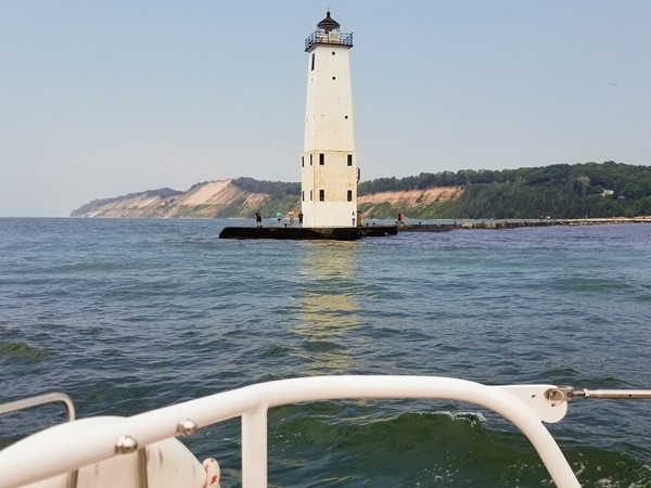 Sailing past the lighthouse in Frankfort Harbor, Lake Michigan